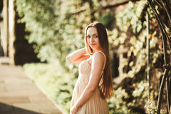 Attractive young woman with long dress enjoying her time outside in park sunset background Stock Photos