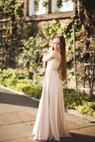 Attractive young woman with long dress enjoying her time outside in park sunset background Stock Photo
