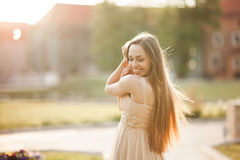 Attractive young woman with long dress enjoying her time outside in park sunset background Royalty Free Stock Images
