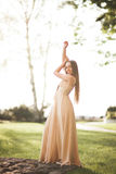 Attractive young woman with long dress enjoying her time outside in park sunset background Stock Images