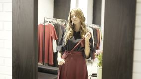 Charming young woman tying her skirt belt in a shop dressing room stock photos