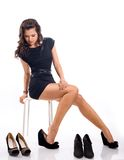 Attractive young woman with long hair chooses shoes Royalty Free Stock Photography
