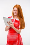Attractive young woman with long red hair using tablet Stock Photography