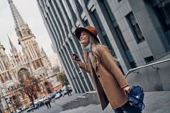 Just stop and enjoy the moment. Attractive young woman looking away and smiling while spending carefree time in the city Royalty Free Stock Image