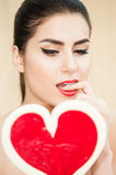 Attractive young woman looking at a candy heart Royalty Free Stock Photo