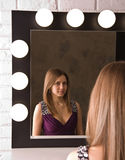 An attractive young woman looking in the mirror Stock Photo