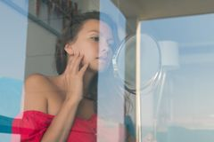 Attractive young woman looking at mirrow behind the glass of window her room royalty free stock photos