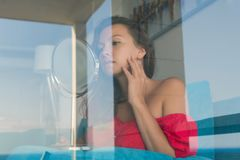 Attractive young woman looking at mirrow behind the glass of window her room stock images
