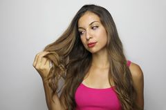 Attractive young woman looking to her long hair. Beautiful girl looks worried / satisfied at the tips of her hair on gray. Background royalty free stock image