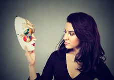 Attractive woman looking at traditional carnival mask stock photos