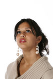 Attractive young woman looking up. Portrait of cute young Hispanic woman wearing a beige sweater looking up Royalty Free Stock Image