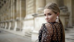 Attractive young woman looks charming on background of old building. Action. Blonde sexy looking over shoulder at camera stock photography