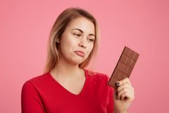 Attractive young woman looks with discontent expression at sweet bar of chocolate, keeps to diet, can`t eat it to be slim and spor. Ty, curves lower lip,  over Royalty Free Stock Photos