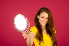 Attractive young woman looks herself in mirror over vibrant pink Stock Photography