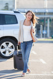 Attractive young woman with luggage is traveling Stock Image