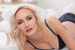 Attractive young woman is luxuriating in bedroom Royalty Free Stock Photography