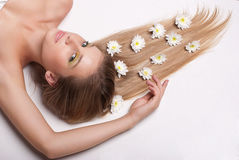 Attractive young woman lying covered with flowers Stock Photo