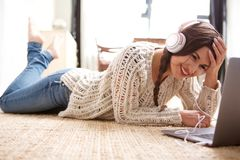 Attractive young woman lying on floor at home with laptop and headphones. Portrait of attractive young woman lying on floor at home with laptop and headphones Stock Photo