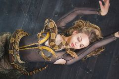 Attractive young woman lying on the floor with a snake on her body stock photography