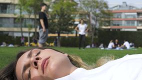 Attractive young woman lying on the grass - Children have fun background in park stock video