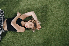 Attractive young woman lying on green grass and looking away Royalty Free Stock Photography