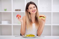Attractive young woman makes a choice between healthy and unheal Royalty Free Stock Photo