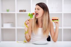 Attractive young woman makes a choice between healthy and unheal Royalty Free Stock Photography