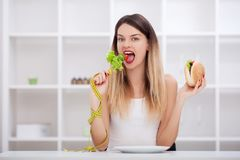 Attractive young woman makes a choice between healthy and unheal Stock Images