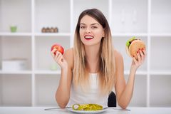Attractive young woman makes a choice between healthy and unheal Royalty Free Stock Images
