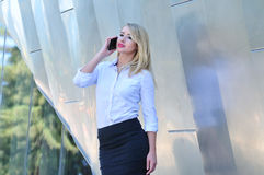 Attractive young woman making business call on her smart phone. Professional corporate woman in business attire talking on mobile phone in the city Royalty Free Stock Photography