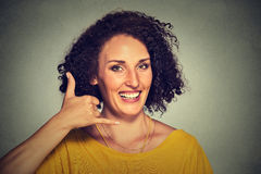 Attractive young woman making a call me sign and smiling. Portrait attractive young woman making a call me sign and smiling isolated on gray wall background Royalty Free Stock Images