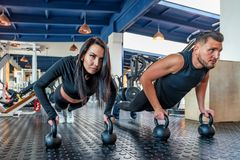 Attractive young woman and man do plank exercise in gym. Young fit couple of trainers doing plank exercise in modern gym royalty free stock images