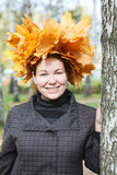 Attractive young woman with maple wreath standing near birch tree Stock Photos