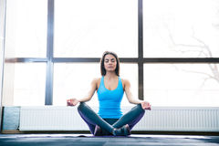 Attractive young woman meditating at gym. Attractive young woman sitting on yoga mat and meditating at gym Stock Image