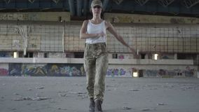 Attractive young woman in military uniform marching on concrete floor in dusty dirty abandoned building toward the. Attractive young woman in military uniform stock footage