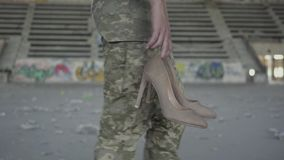 Attractive young woman in military uniform walking slowly in dusty dirty abandoned building carrying high-heeled shoes. Attractive young woman in military stock video footage