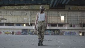Attractive young woman in military uniform walking slowly in dusty dirty abandoned building carrying high-heeled shoes. In hands looking in camera. The concept stock footage