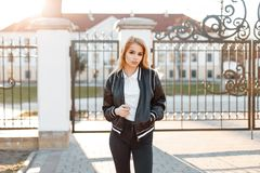 Attractive young woman model in a spring stylish jacket in trendy jeans in white shirt poses near the vintage gate. Against the background of a white building stock image