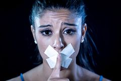 Attractive young woman mouth sealed on adhesive tape and silence gesture stock photos