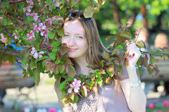 Attractive young woman  near flowered tree. Attractive young woman smiling near flowered tree Royalty Free Stock Photos