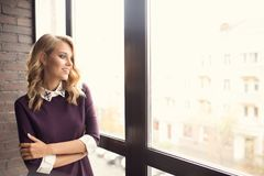 Attractive young woman near window Stock Photos