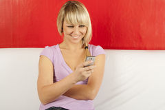 Attractive Young Woman On The Couch With The Phone Royalty Free Stock Photo