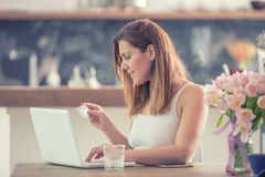 Attractive young woman online shopping using computer and credit card in home kitchen royalty free stock photos