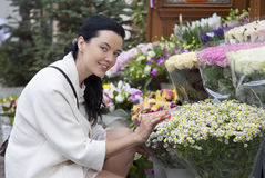 Attractive young woman in outdoors flower-shop Stock Photos