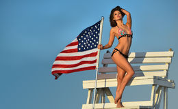 Attractive young woman with perfect slim fit body in bikini posing on the lifeguard tower. Royalty Free Stock Photos