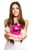 Attractive young woman with a piggy bank on a white background c Stock Images