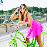Attractive young woman in pink dress on a bicycle Stock Images
