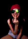 Attractive young woman in a pink knitted cap and sunglasses, licking her middle finger on a dark background Stock Image