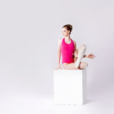 Attractive young woman in pink leotard on a white Stock Images
