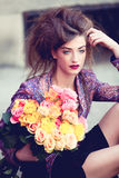 Attractive young woman with pink roses. Outdoor on street Royalty Free Stock Image